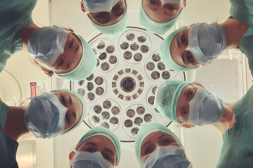 Eight health care professionals gather around unseen patient in operating room to symbolize a systems thinking response to Covid.