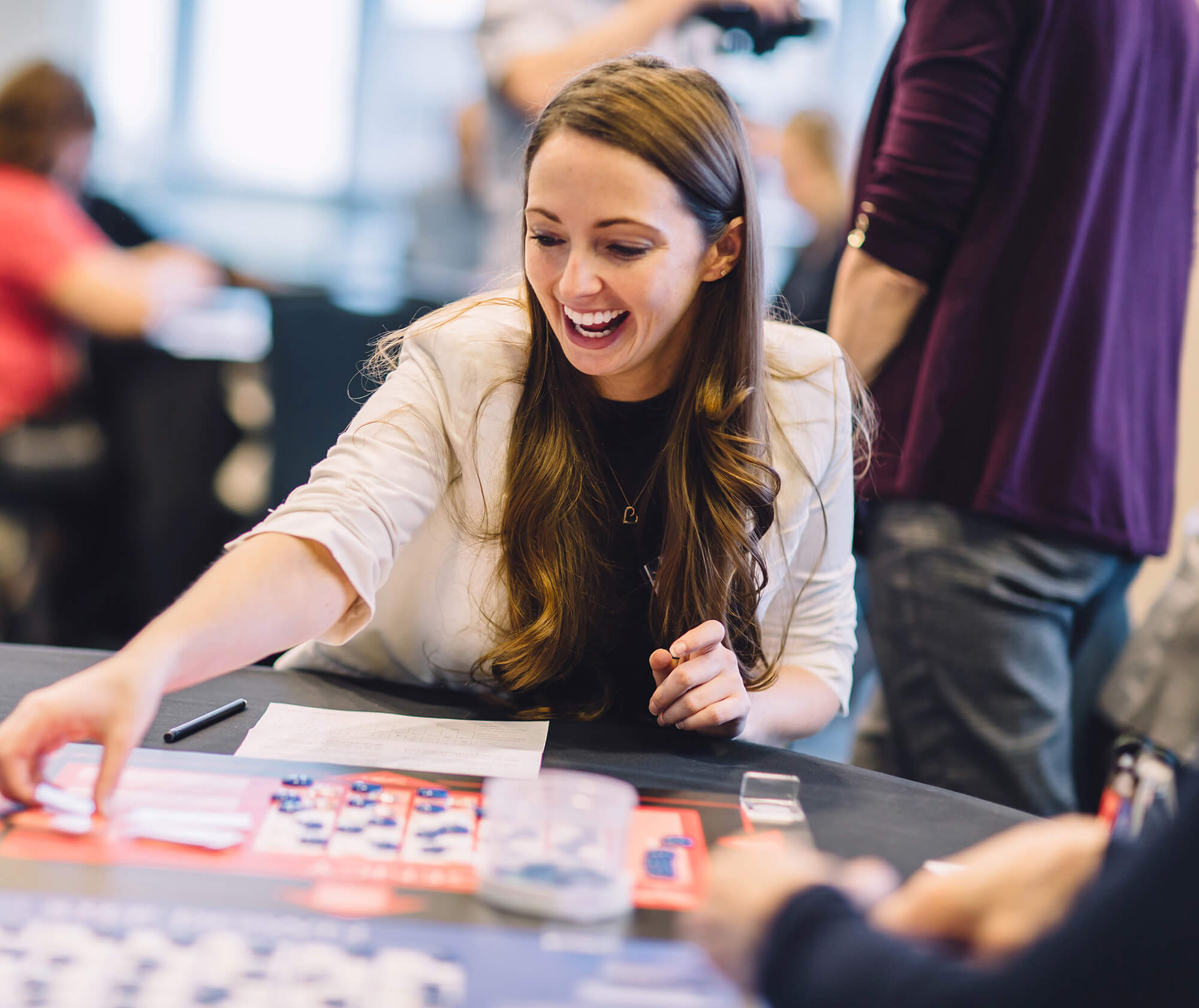 Young woman seated at table smiles and gestures while playing tabletop simulation game Friday Night at the ER