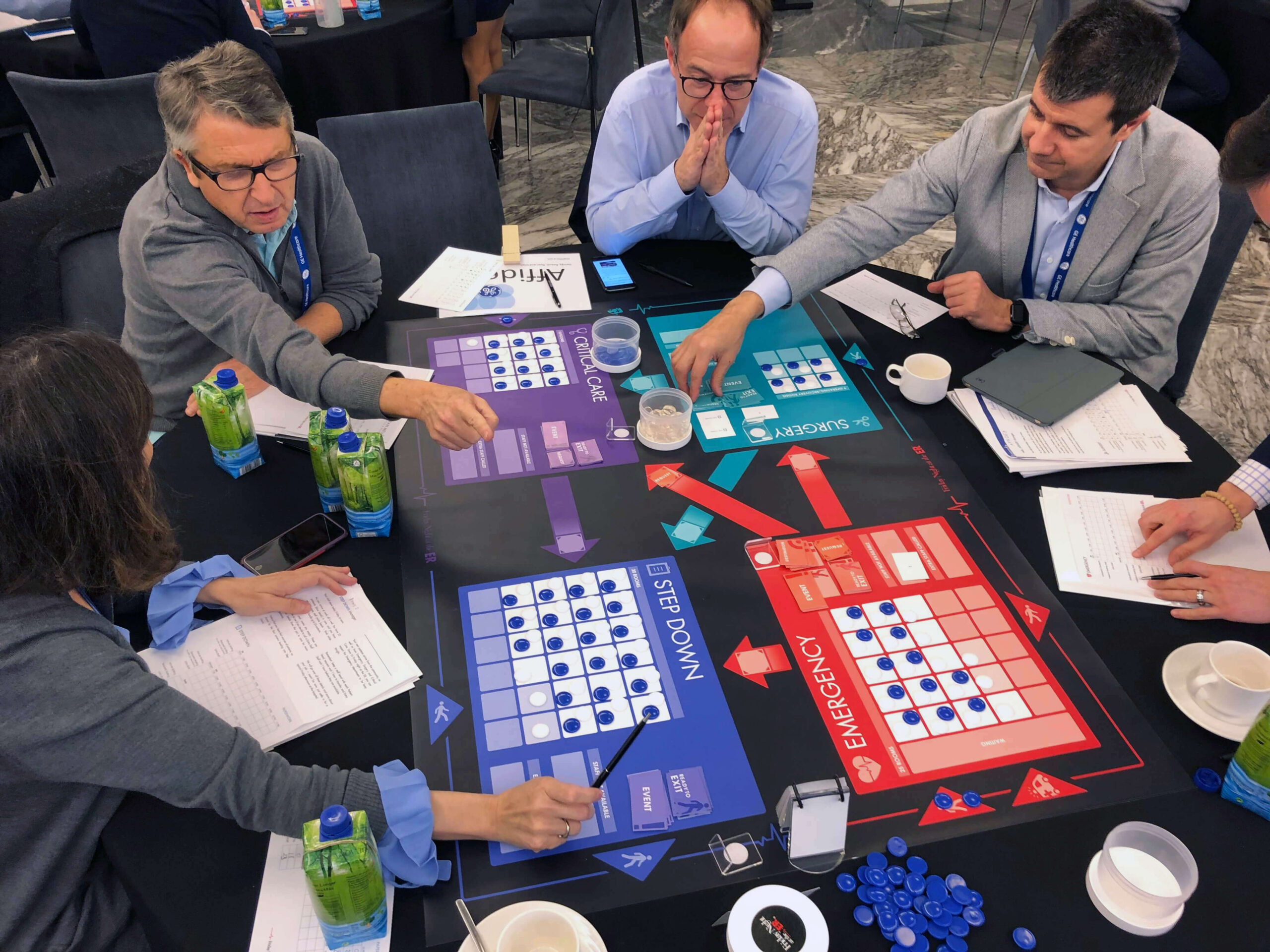 Four managers in business attire play a tabletop simulation game as a team building activity and to break down silo thinking