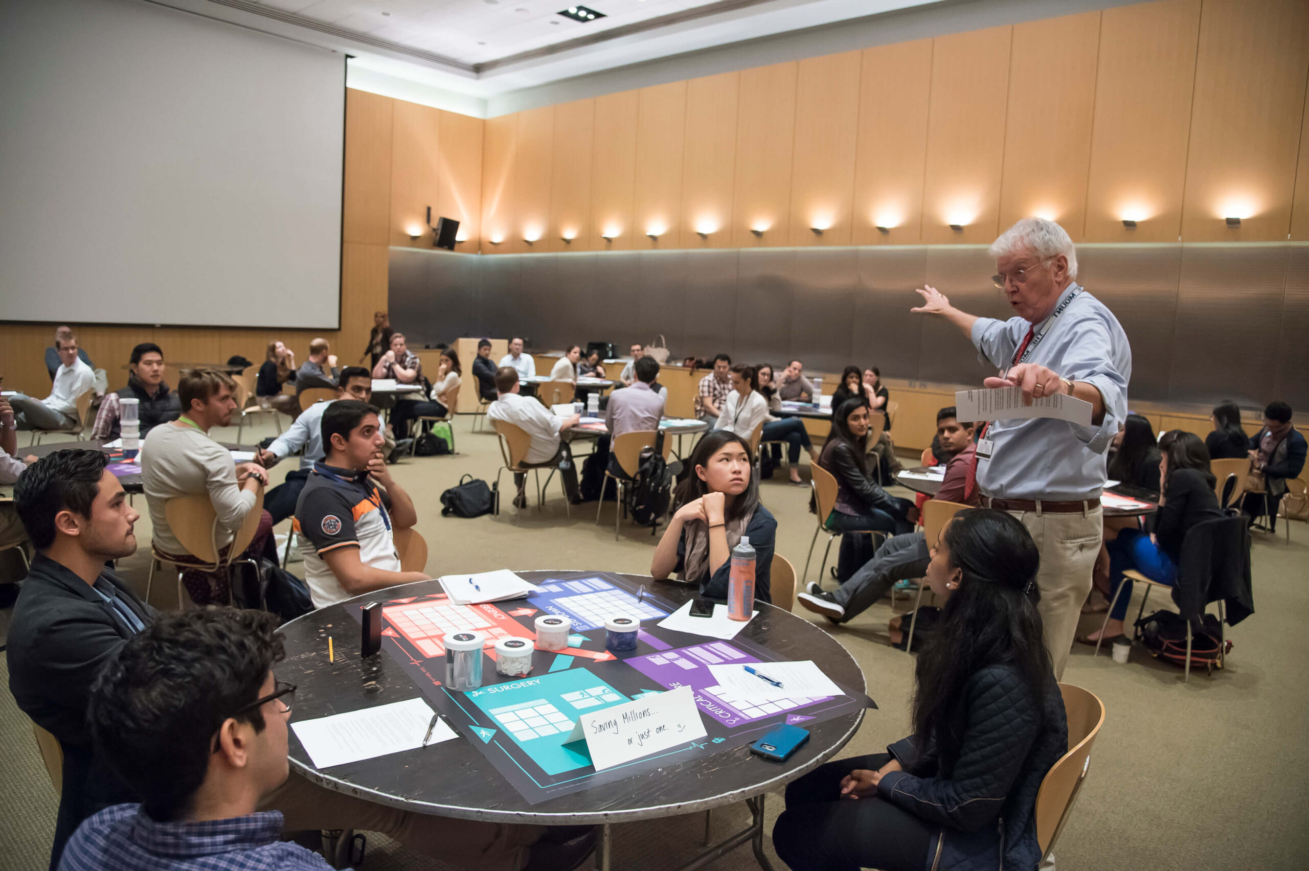 William Ward, Associate Professor from the Johns Hopkins University Bloomberg School of Public Health leads a student discussion following a round of game play of Friday Night at the ER