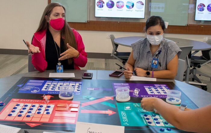 Two female students from Auburn University play Friday Night at the ER tabletop game as an interprofessional activity